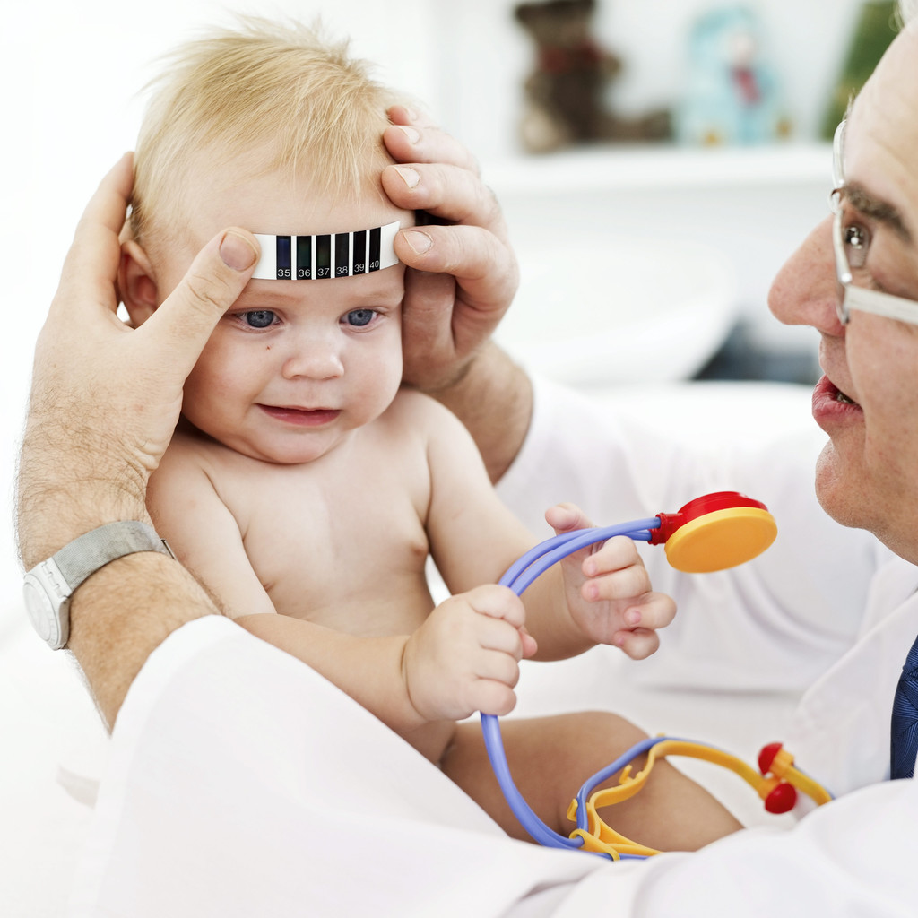 Doctor Applying a Thermometer to a Baby's (12-18) Forehead